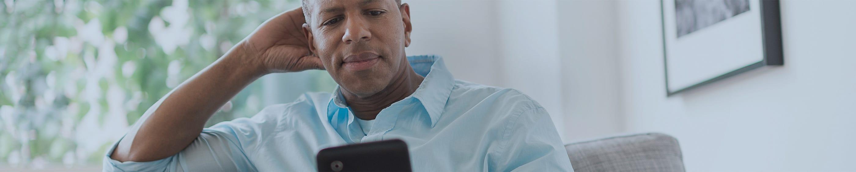 Un padre leyendo su tableta en el sofá